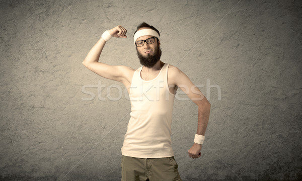 Fiatal férfi mutat izmok fiatalember szakáll Stock fotó © ra2studio
