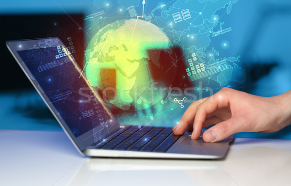 Hand using laptop with worldwide reports links and statistics concept Stock photo © ra2studio