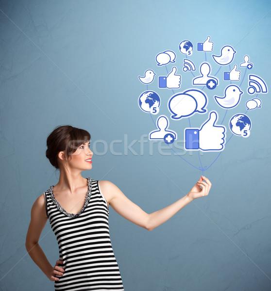 Pretty woman holding social icon balloon Stock photo © ra2studio
