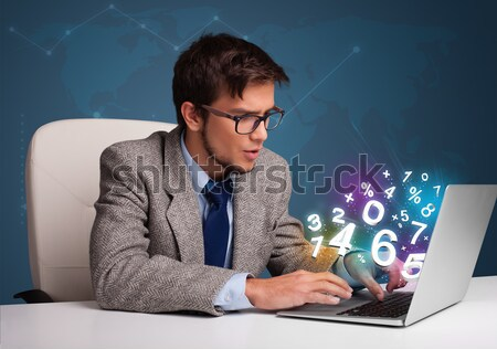 Handsome young man sitting at desk and typing on laptop with 3d numbers comming out Stock photo © ra2studio