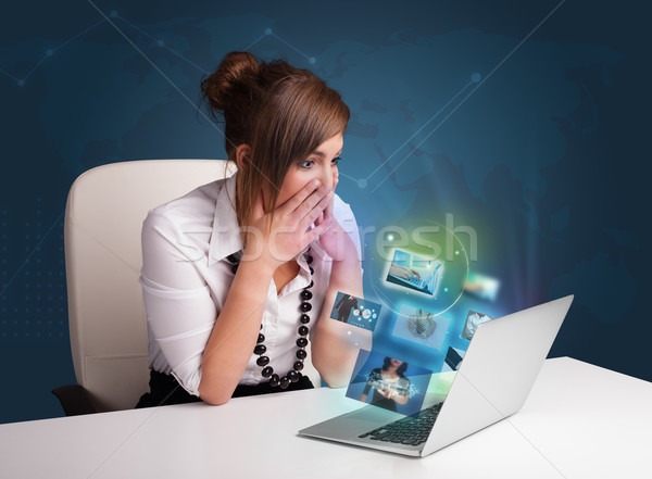 Beautiful young girl sitting at desk and watching her photo gallery on laptop Stock photo © ra2studio