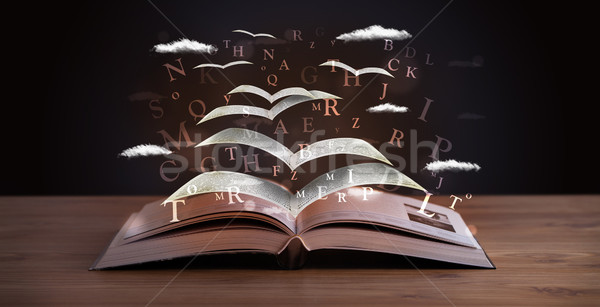 Pages and glowing letters flying out of a book  Stock photo © ra2studio