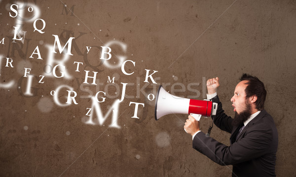 Man in shirt shouting into megaphone and text come out Stock photo © ra2studio
