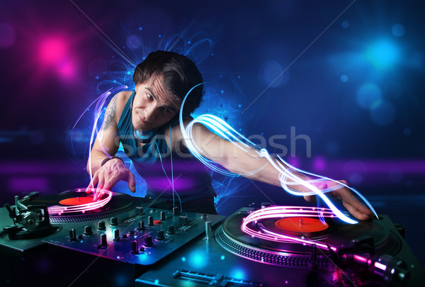 Disc jockey playing music with electro light effects and lights Stock photo © ra2studio