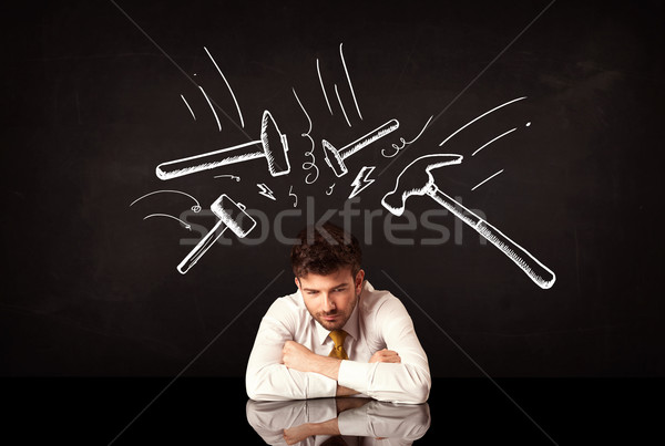 Depressed businessman sitting under hammer marks Stock photo © ra2studio