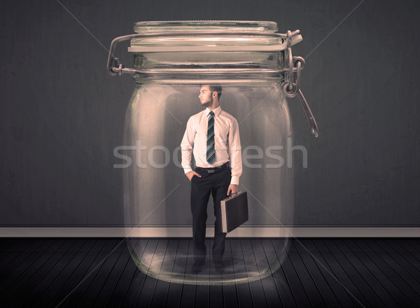 Stock photo: Businessman trapped into a glass jar concept