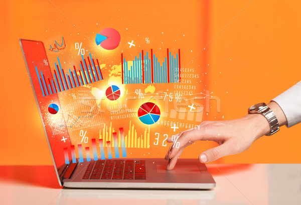 Stock photo: Hand typing on modern laptop notebook computer with graph icons