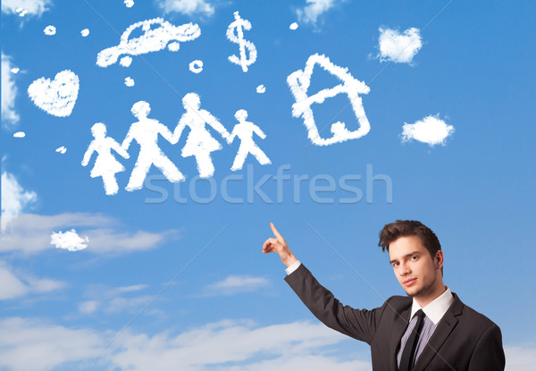 Businessman daydreaming with family and household clouds  Stock photo © ra2studio