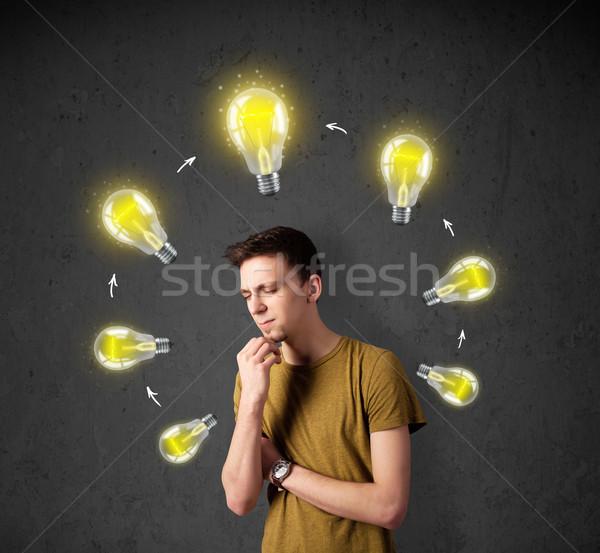Young man thinking with lightbulb circulation around his head Stock photo © ra2studio