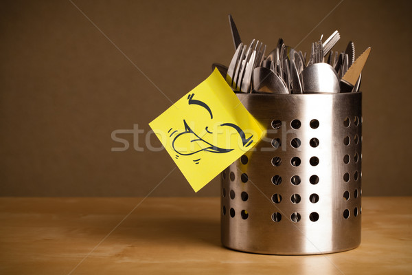 Post-it note with smiley face sticked on cutlery case Stock photo © ra2studio