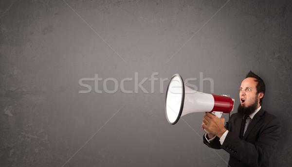 Guy shouting into megaphone on copy space background Stock photo © ra2studio