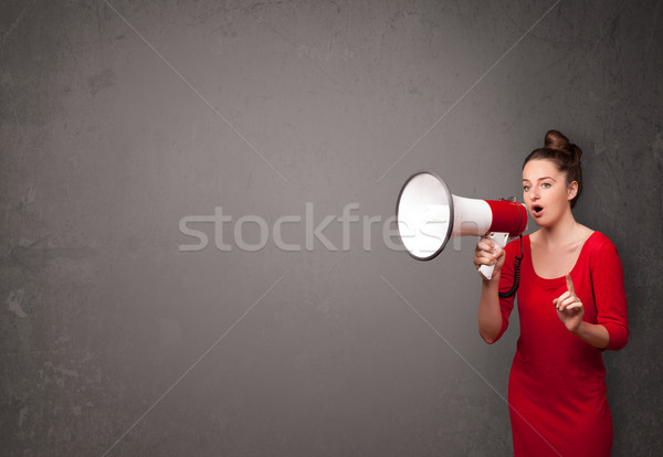 Girl shouting into megaphone on copy space background Stock photo © ra2studio