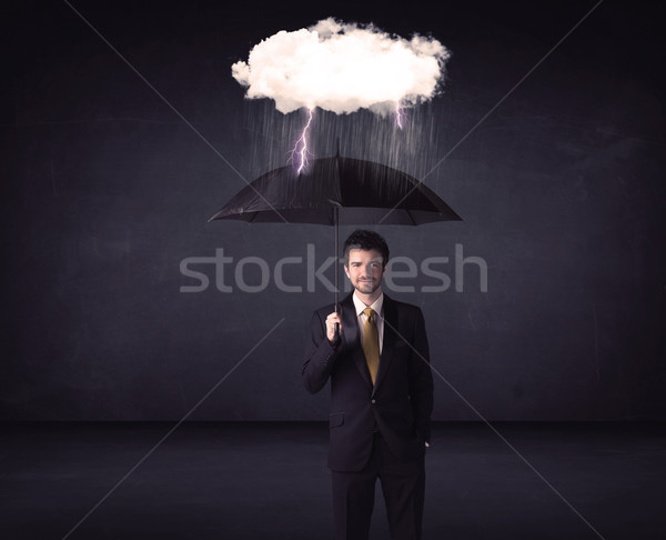 Businessman standing with umbrella and little storm cloud Stock photo © ra2studio