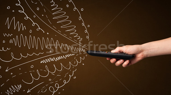 Hand with remote control and curly lines Stock photo © ra2studio