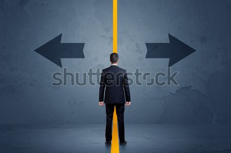 Business person choosing between two options separated by a yellow border arrow Stock photo © ra2studio
