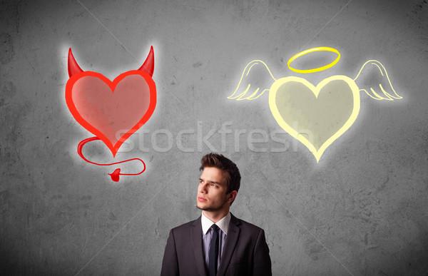 Businessman standing between angel and devil hearts Stock photo © ra2studio