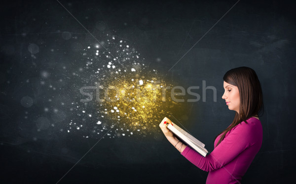 Stock photo: Young lady reading a magical book