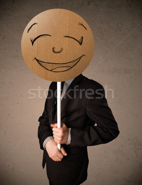 Businessman holding a smiley face board Stock photo © ra2studio