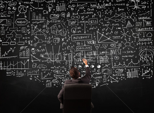 Businessman sitting in front of a blackboard with charts Stock photo © ra2studio