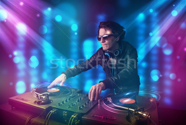 Dj mixing music in a club with blue and purple lights Stock photo © ra2studio