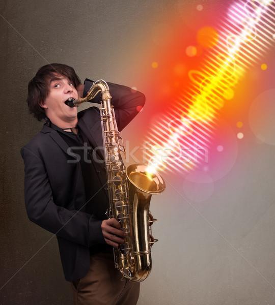 Młody człowiek gry saksofon kolorowy dźwięku fale Zdjęcia stock © ra2studio