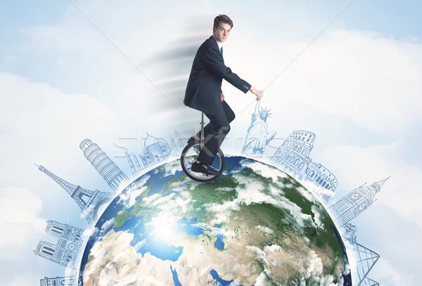 Man riding unicycle around the globe with major cities Stock photo © ra2studio