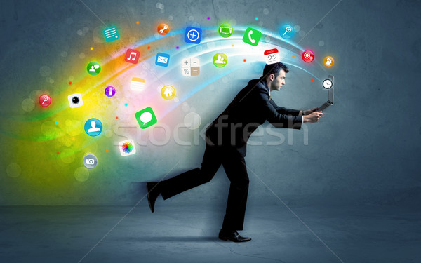 Running businessman with application icons from device Stock photo © ra2studio