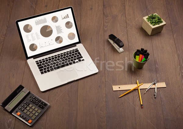 Pie chart graph icons on laptop screen with office accessories  Stock photo © ra2studio