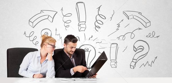 Young businessman and businesswoman brainstorming with drawn arrows and symbols Stock photo © ra2studio
