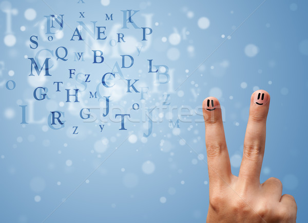 Happy smiley fingers looking at mixture of bokeh letters Stock photo © ra2studio