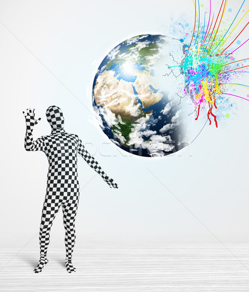 Funny man in body suit looking at colorful splatter earth Stock photo © ra2studio