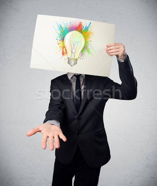 Businessman holding a cardboard with paint splashes and lightbul Stock photo © ra2studio