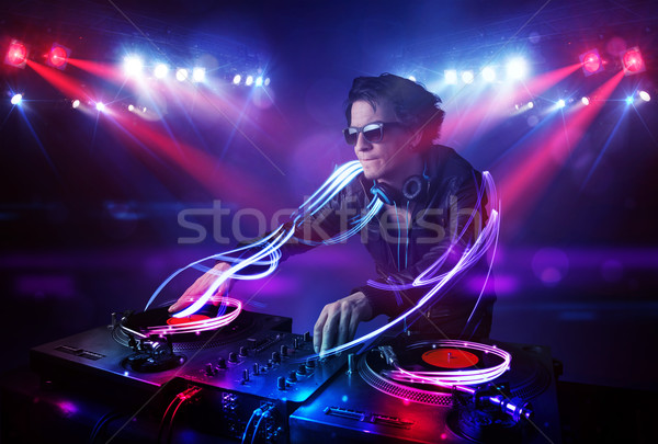 Disc jockey playing music with light beam effects on stage Stock photo © ra2studio