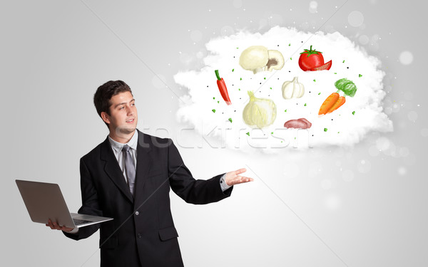 Handsome man presenting a cloud of healthy nutritional vegetable Stock photo © ra2studio