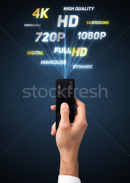 Stock photo: Hand with remote control and multimedia properties