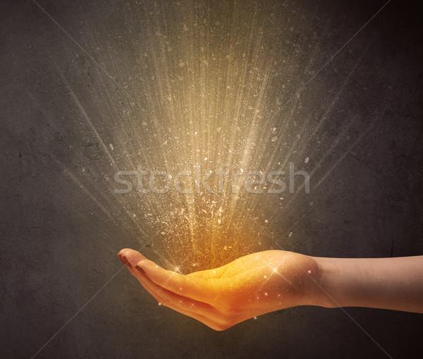 Hand holding yellow light Stock photo © ra2studio