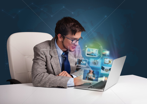 Vonzó fiatalember ül asztal néz fotó Stock fotó © ra2studio
