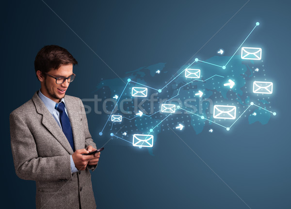 Young man holding a phone with arrows and message icons Stock photo © ra2studio