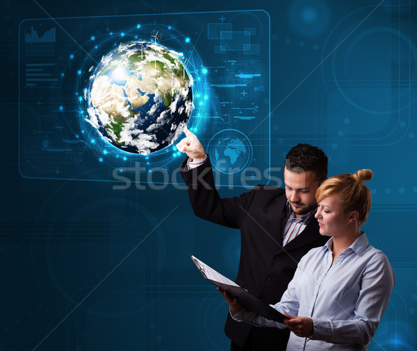 Young couple touching high-tech 3d earth panel Stock photo © ra2studio