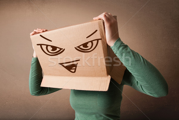 Young woman gesturing with a cardboard box on her head with evil Stock photo © ra2studio
