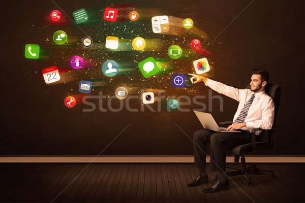Business man sitting in office chair with laptop and colorful ap Stock photo © ra2studio