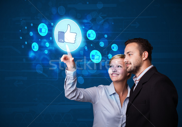 Young business couple pressing thumbs up button on modern social Stock photo © ra2studio