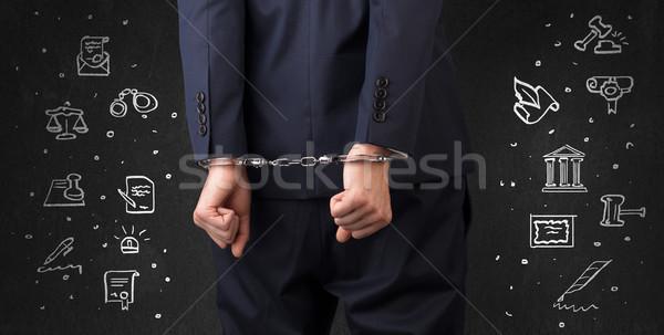 Symbols of courthouse with handcuffed man Stock photo © ra2studio