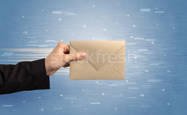 Hand holding envelope with arrows around Stock photo © ra2studio