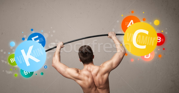 Gespierd man kleurrijk vitamine gewichten Stockfoto © ra2studio