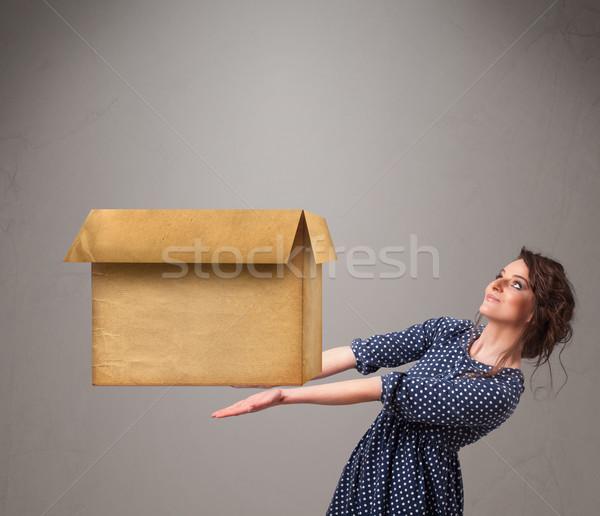 Young woman holding an empty cardboard box Stock photo © ra2studio