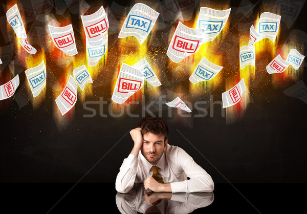 Depressed businessman sitting under burning tax and bill papers Stock photo © ra2studio