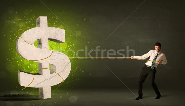 Business man pulling a big green dollar sign Stock photo © ra2studio