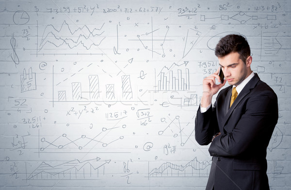 Salesman standing with drawn graph charts Stock photo © ra2studio