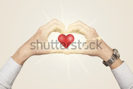 Hands creating a form with shining heart Stock photo © ra2studio